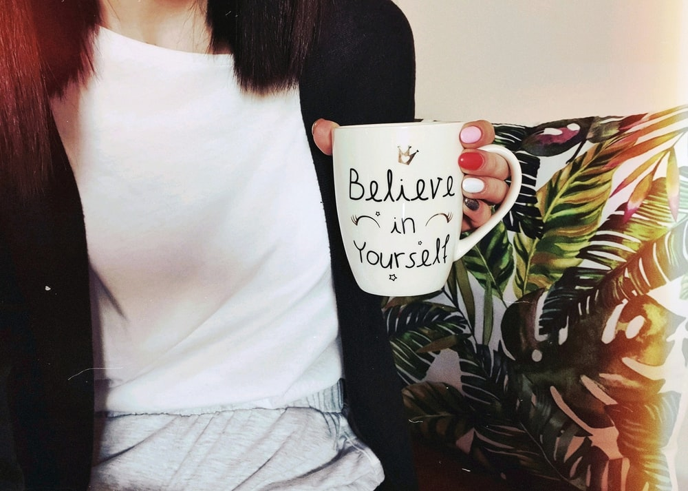 woman wearing black cardigan holding mug