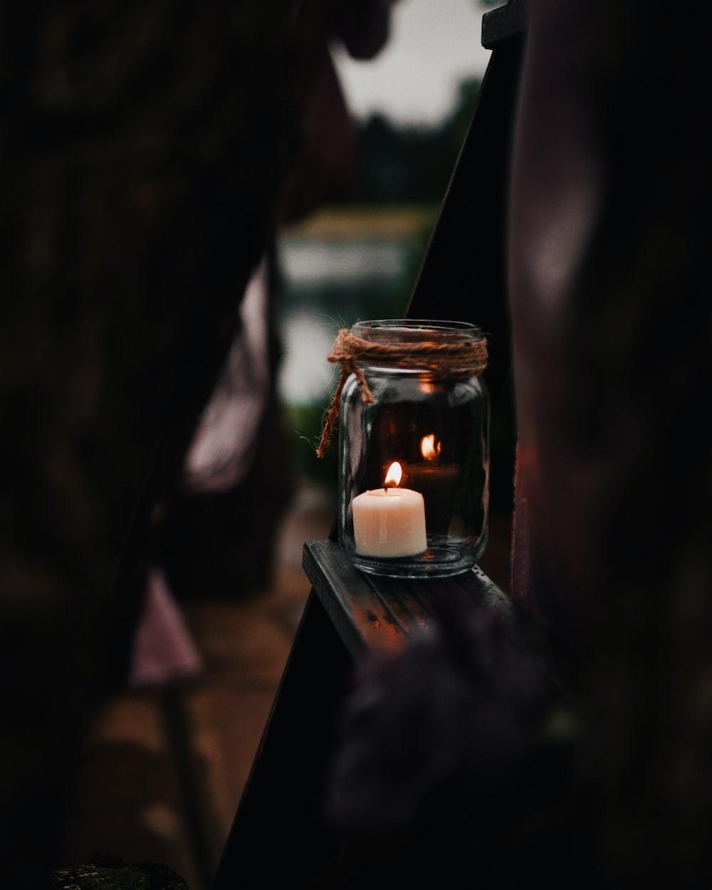 white tealight candle inside clear mason jar