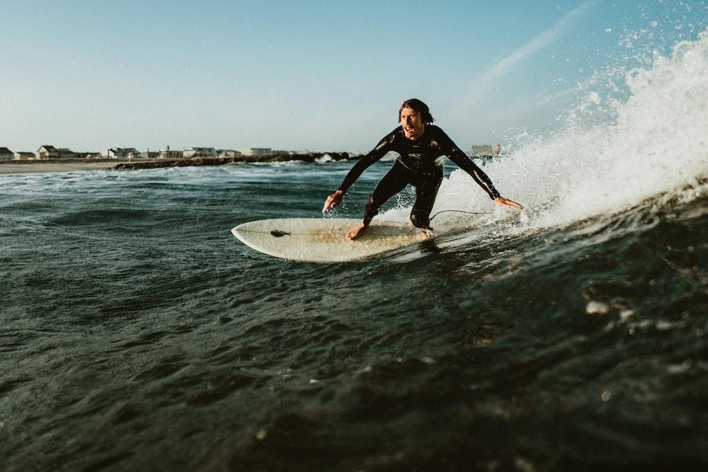 man playing surfboarding during daytime