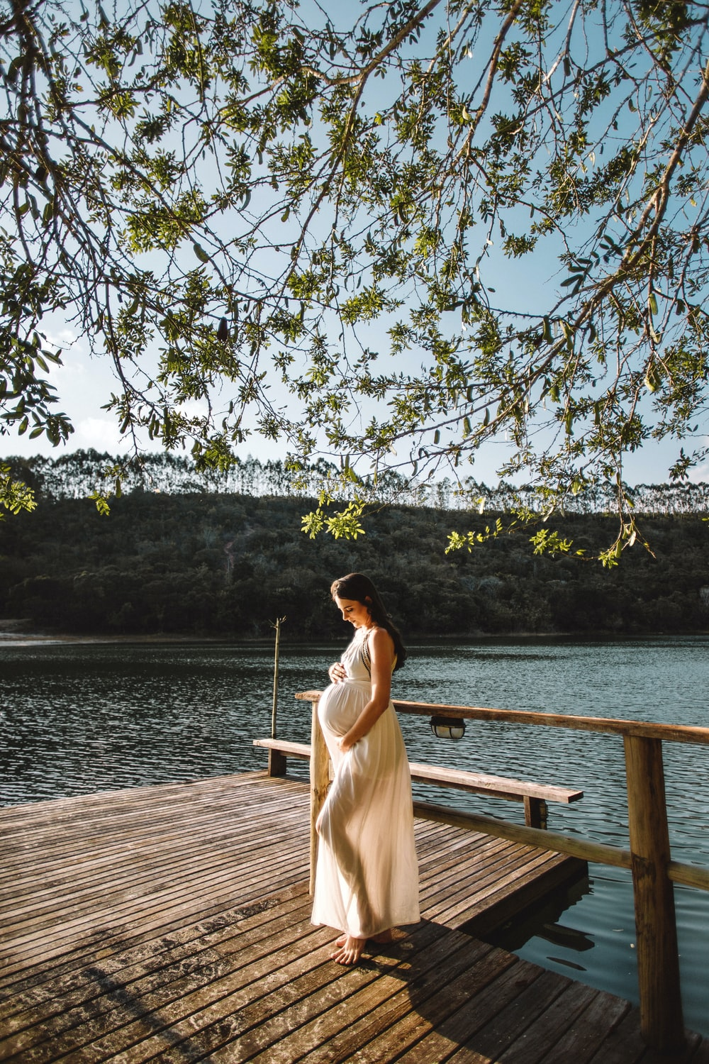 pregnant woman standing on wooden dock under tree