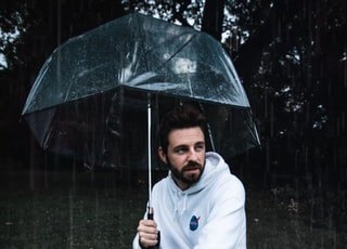 man in white tracksuit under umbrella