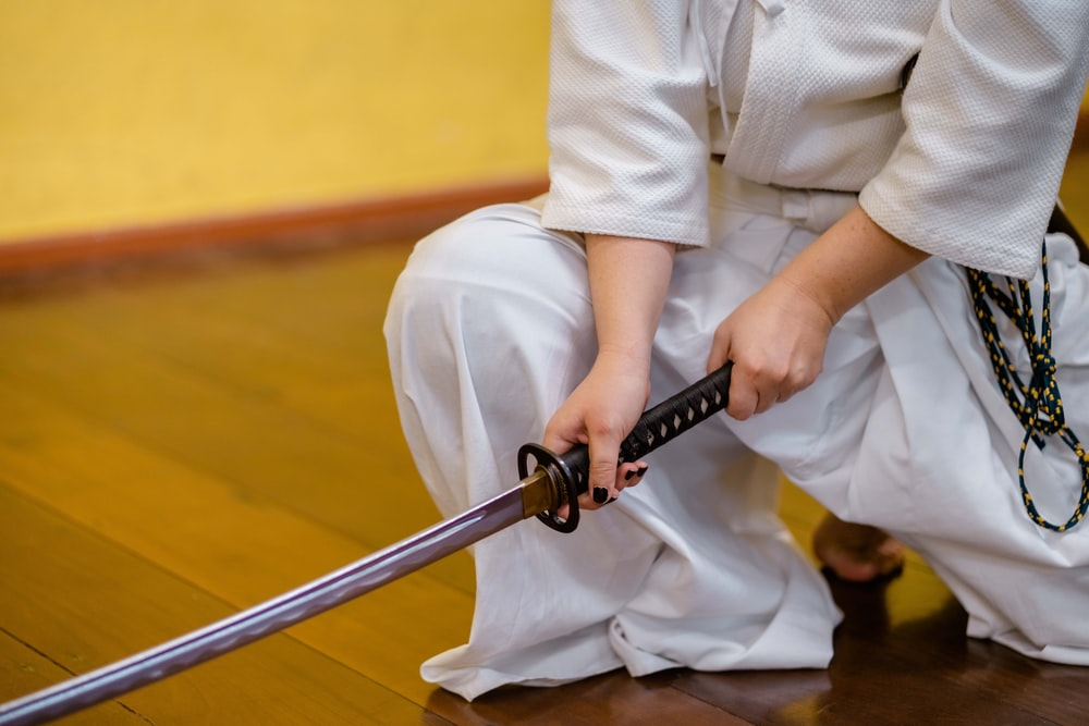 man holding black and gray katana