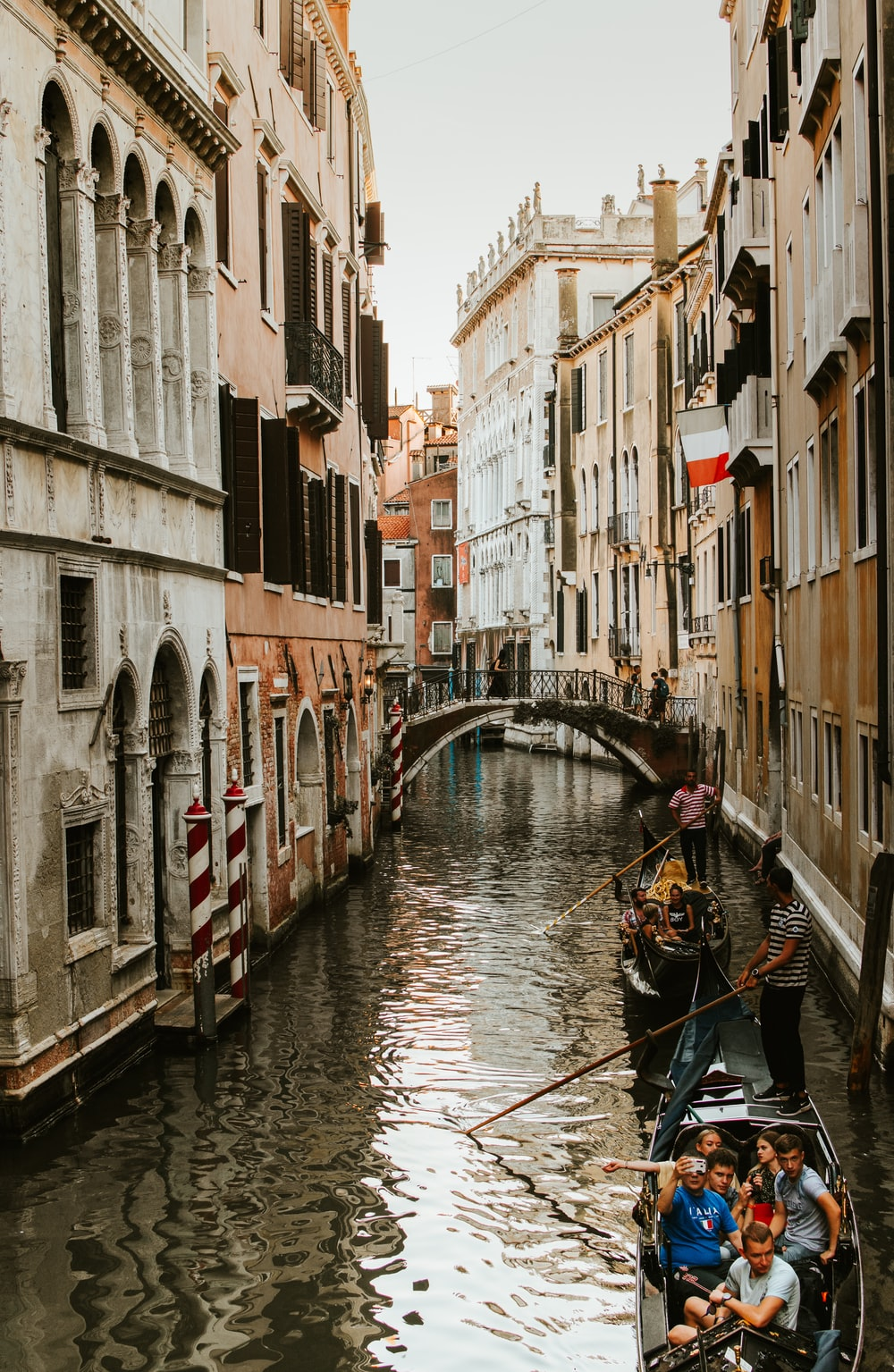 people riding boats floating on canal between buildings