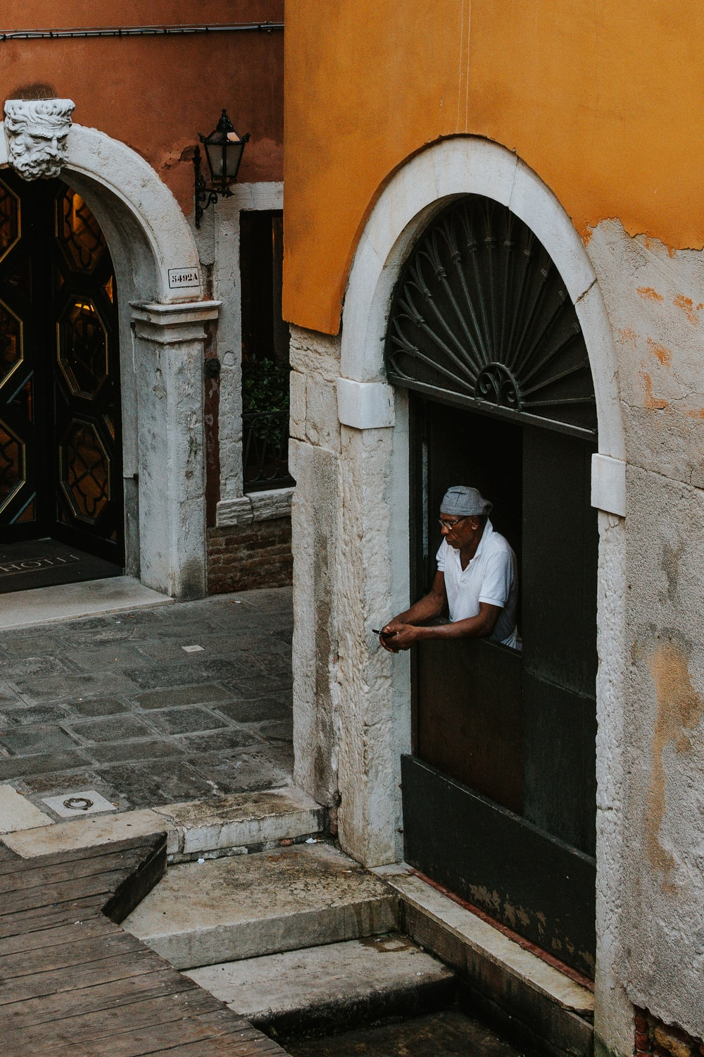 man in white polo shirt in front of gate