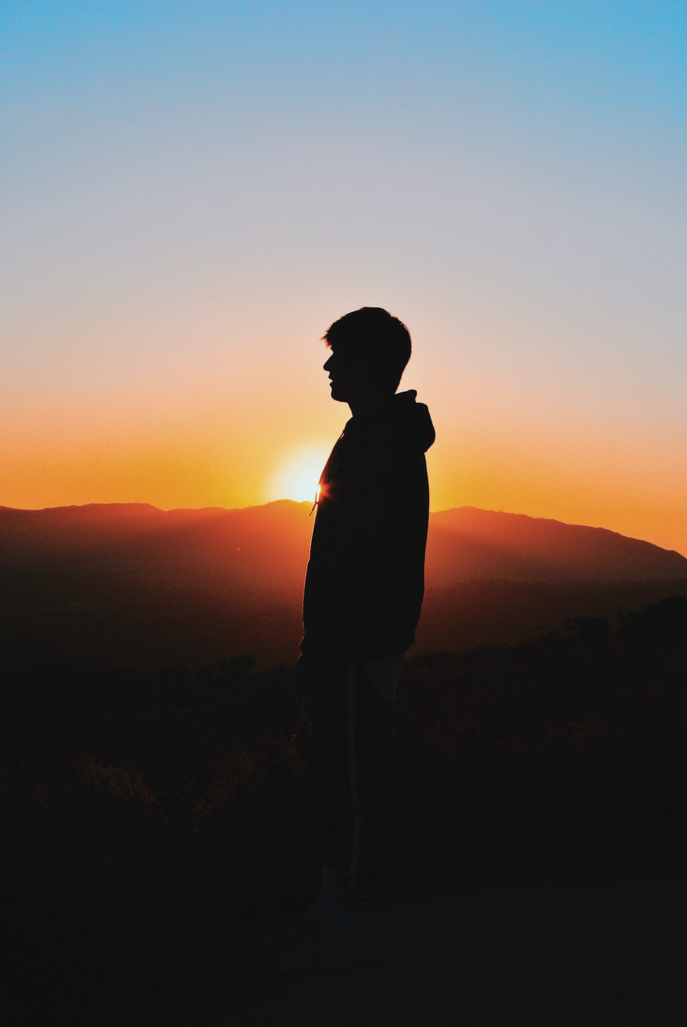 man wearing hoodie during golden hour