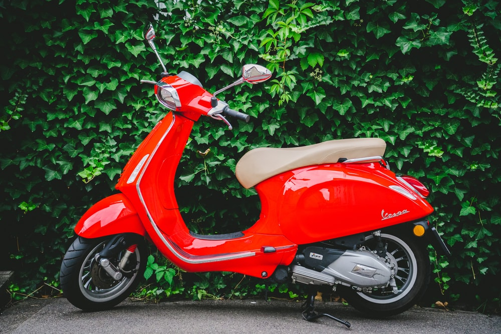 red motor scooter on focus photography