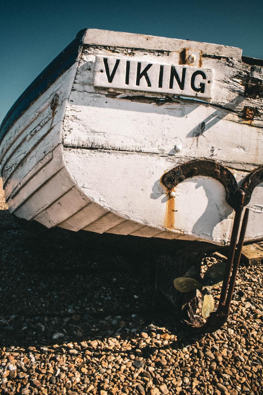 white wooden boat on black sand