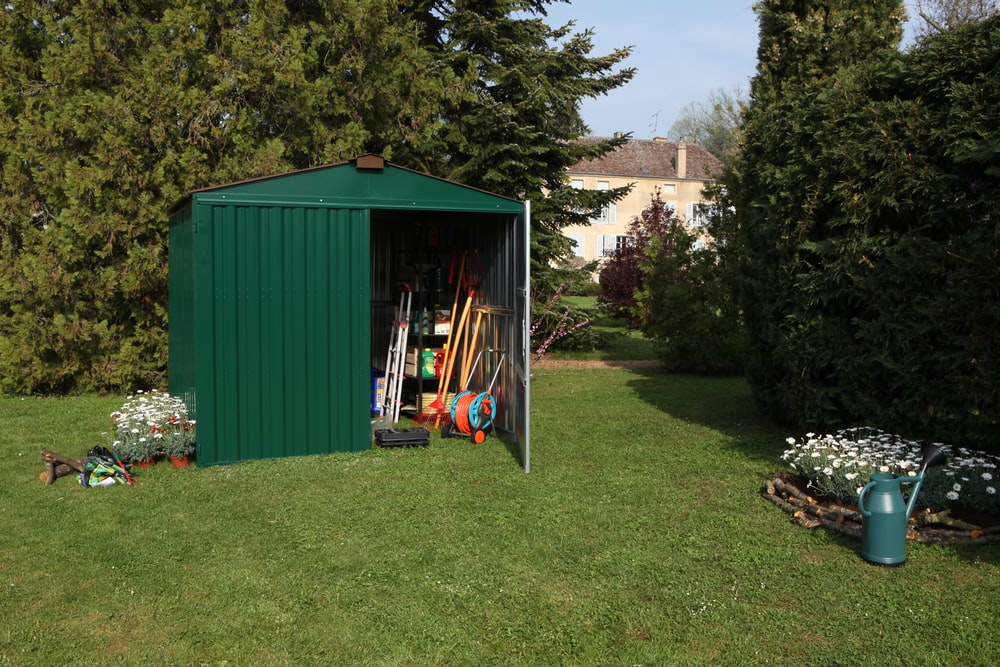 half opened green shed on grass near trees