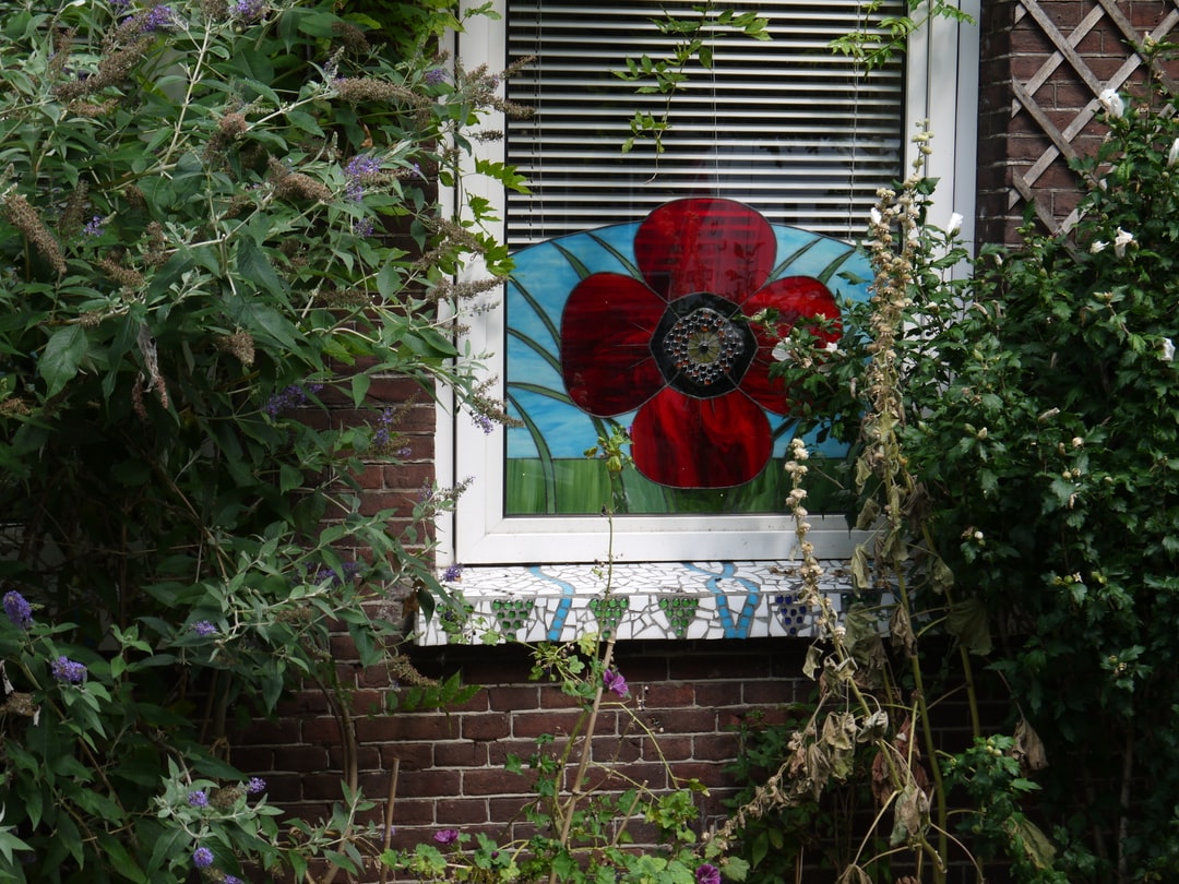 Free urban photo of Amsterdam city - picture of hollyhocks and butterfly bush in front of an artificial glass-flower decoration in the window behind the glass; it is in the streets of Amsterdam, district De Pijp; urban nature photo, Fons Heijnsbroek, August 2019 - The Netherlands.