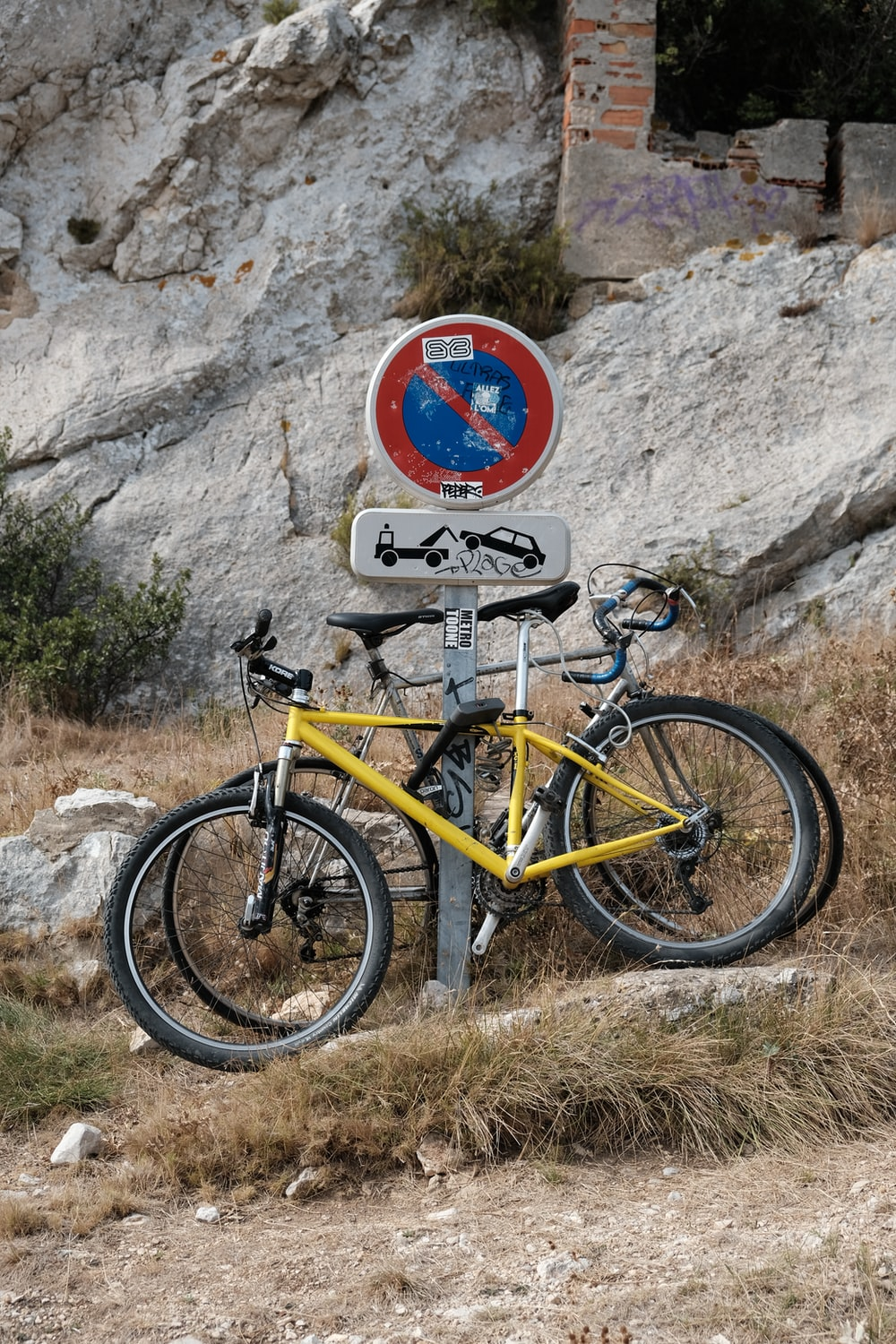 two bikes parked beside signboard on post