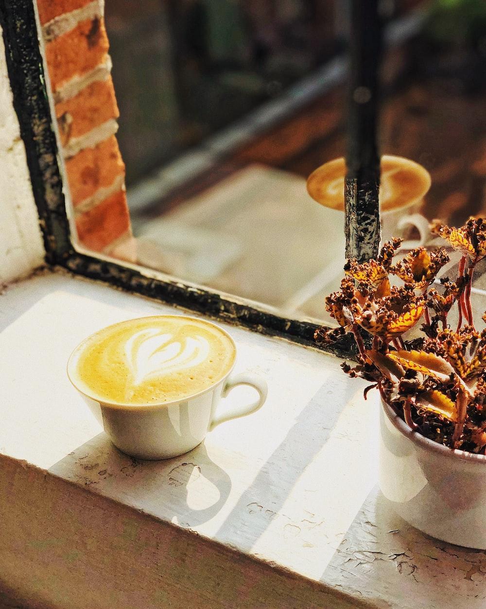 white teacup near on window