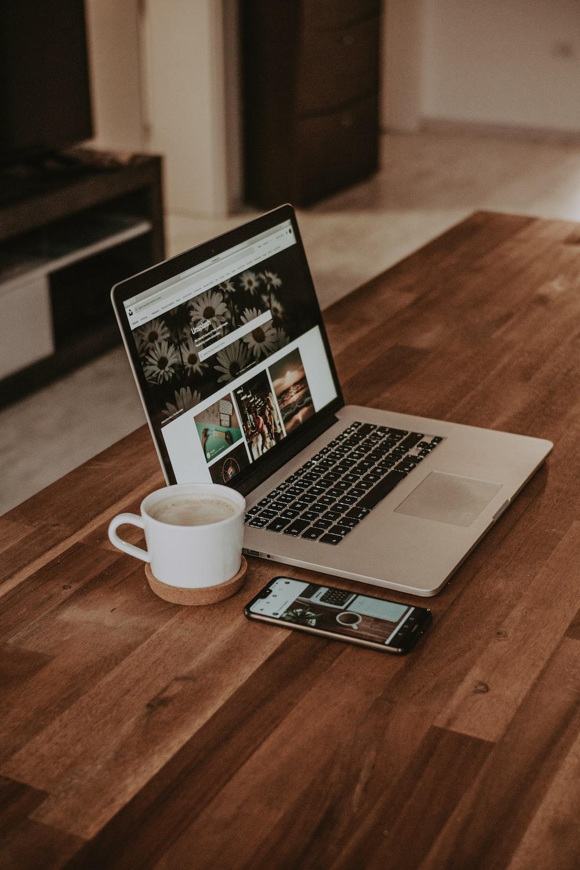 turned-on MacBook Pro beside ceramic mug on table