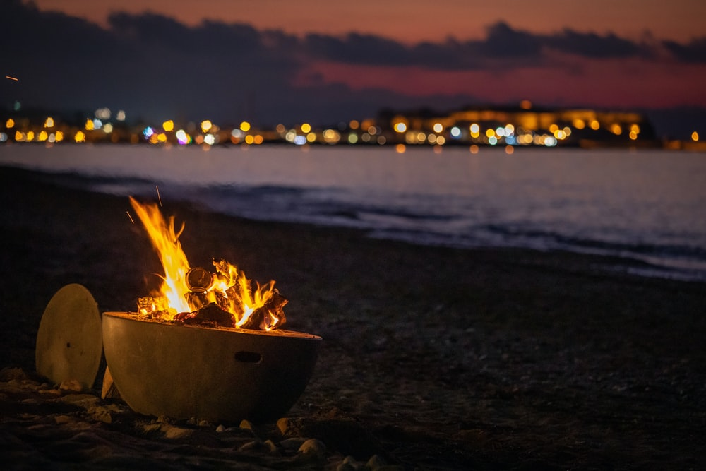 fire in fire pit on shore during golden hour
