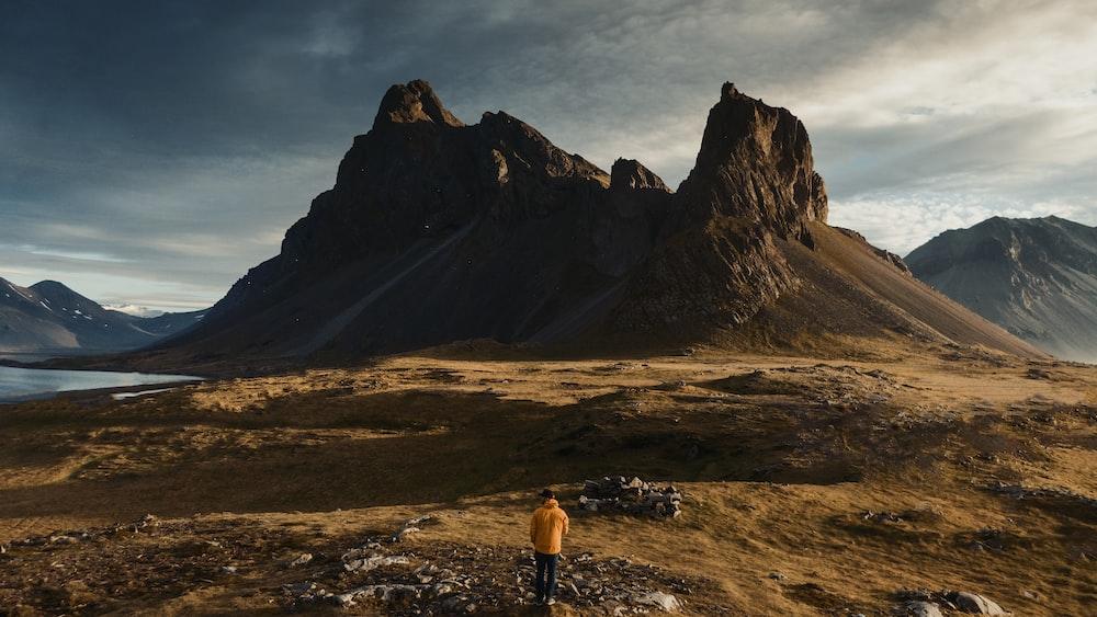 man stands near mountain