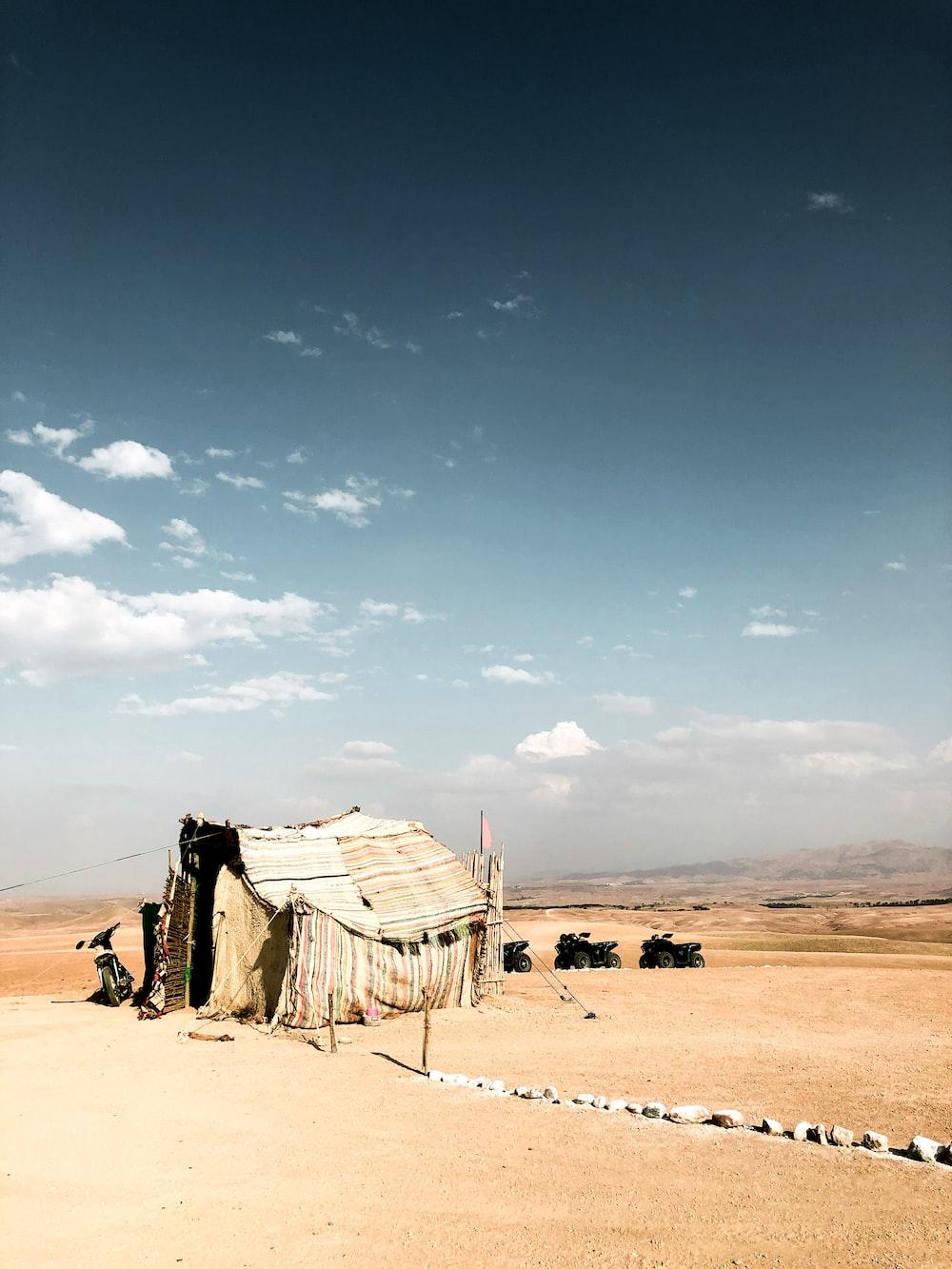 hut on dunes during daytime