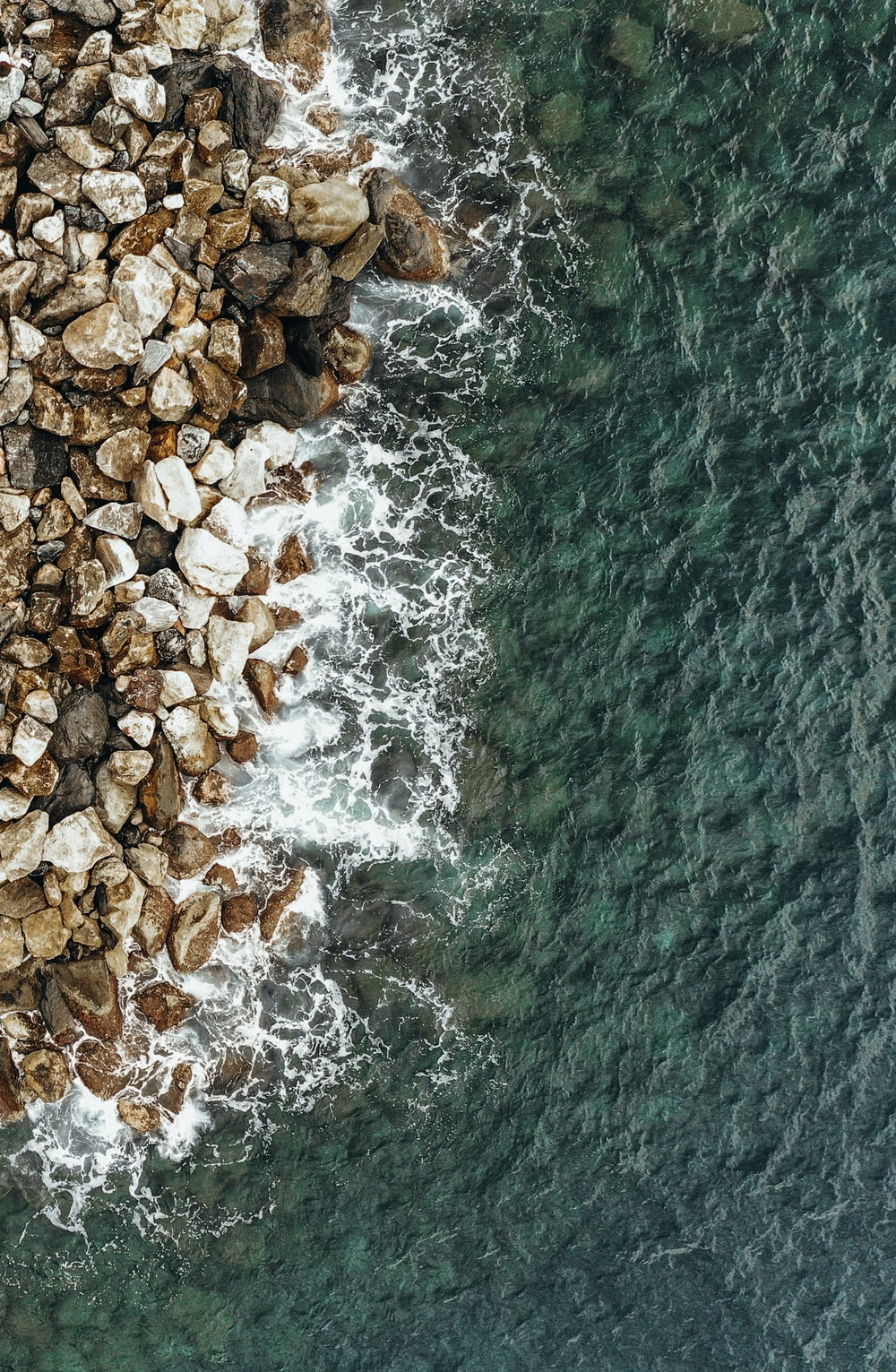 aerial photography of brown rocks near body of water during daytime