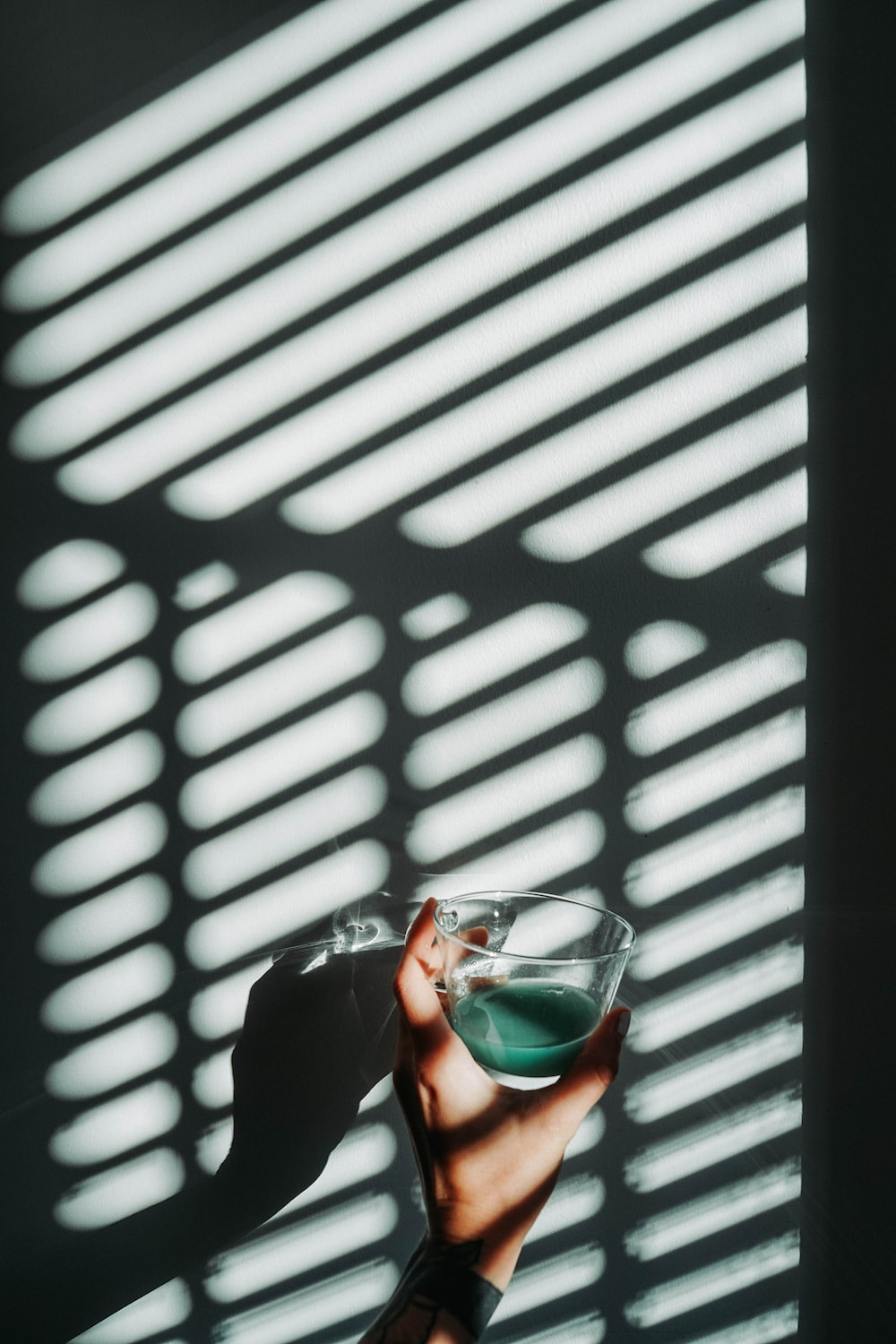 person holding drinking glass cup with green liquid