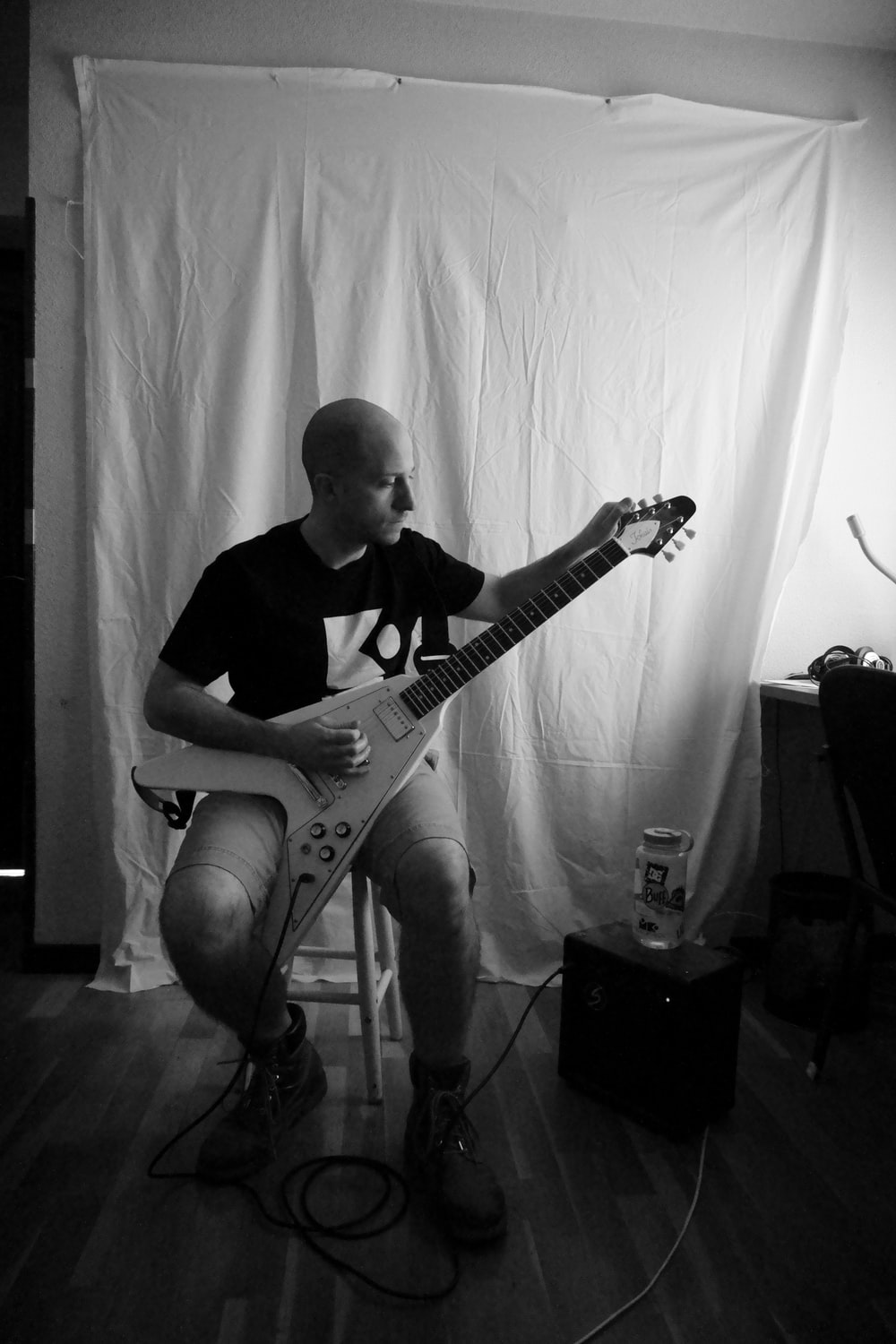 grayscale photography of man sitting while playing electric guitar