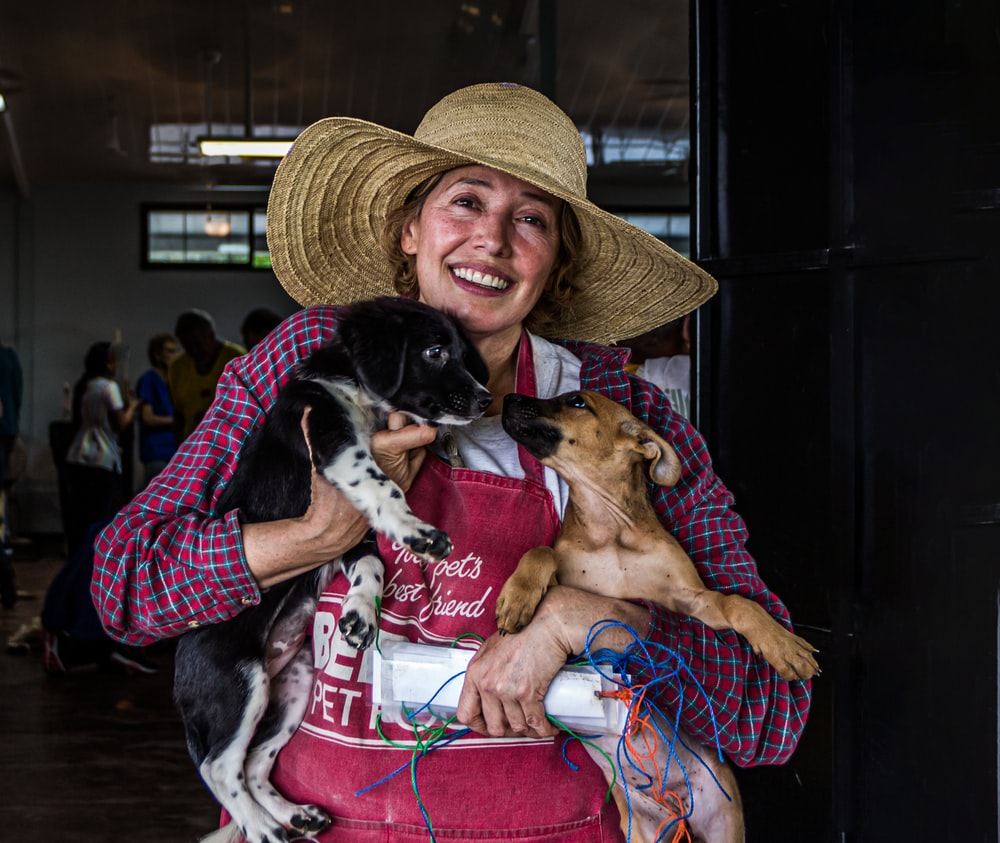 woman in sun hat carrying to puppies