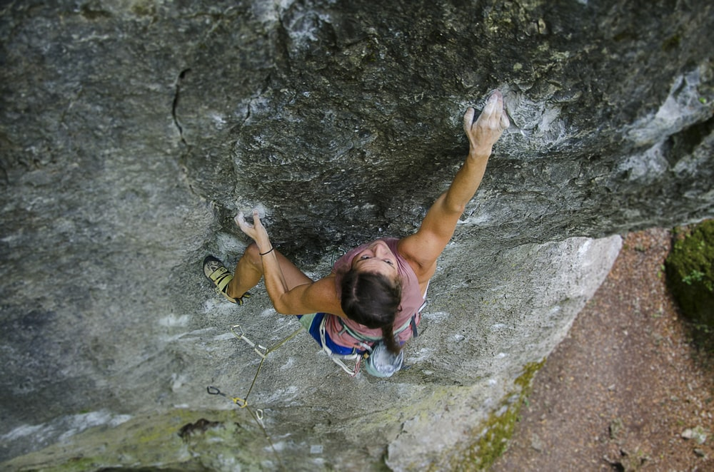 woman wearing pink tank top climbing on stone