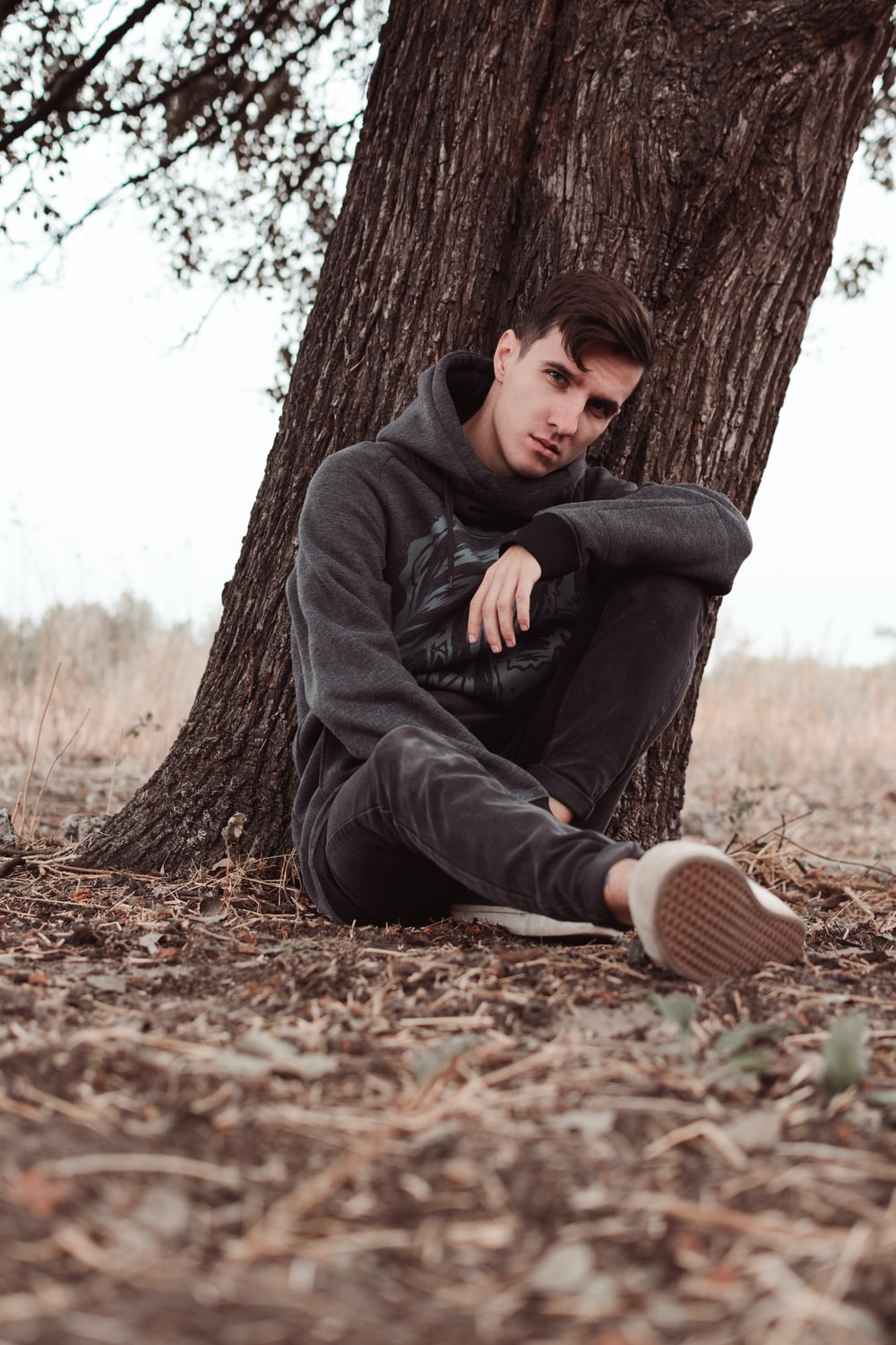 man leaning on tree during daytime. Who needs you to help facilitate his monologue on his emotions