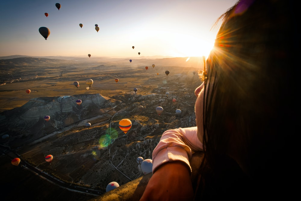 hot air balloons above woman