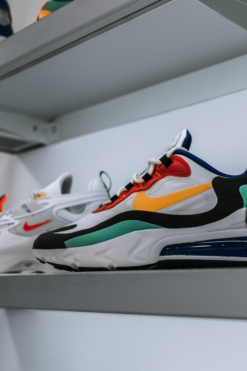 white and multicolored Nike Air Max shoe on shelf photo