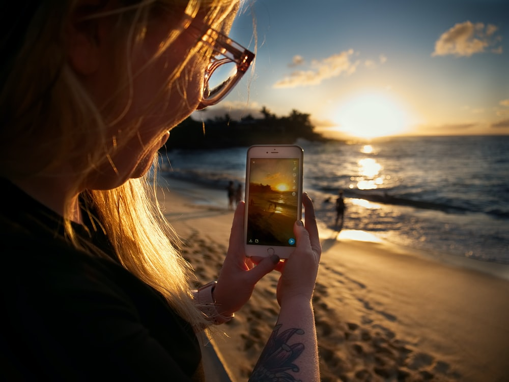 woman taking picture of beach