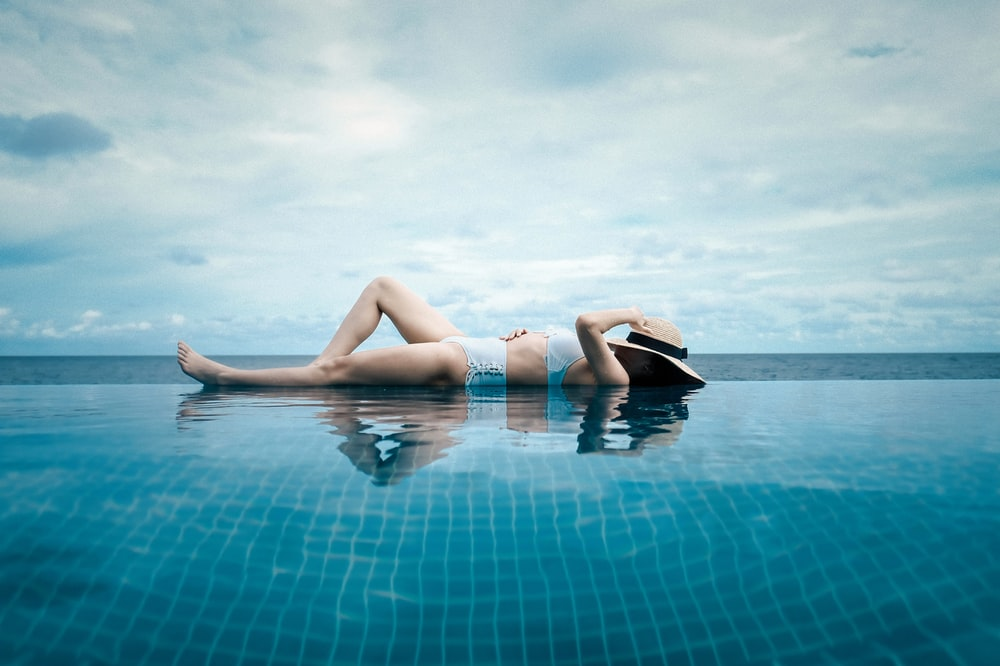 woman lying at the side of the pool during day