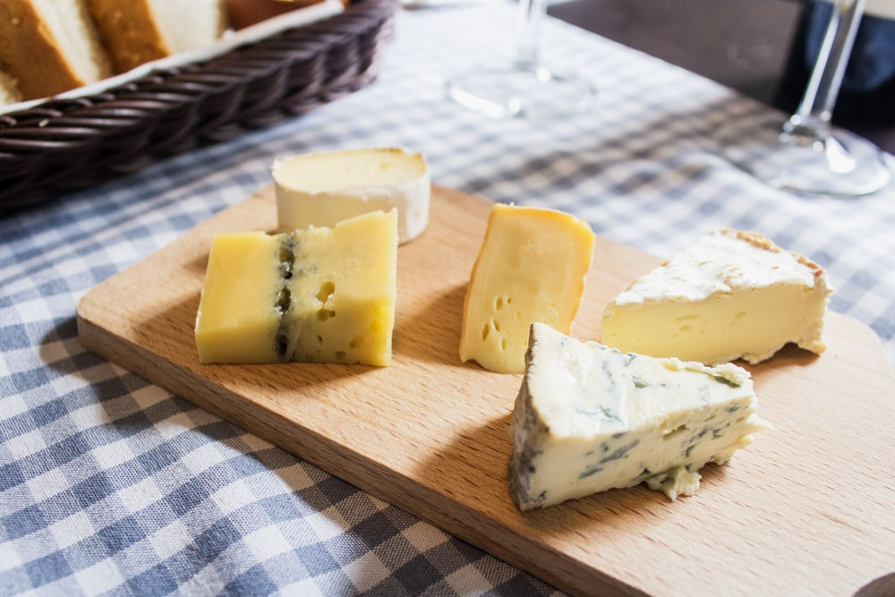 assorted cheeses on chopping board