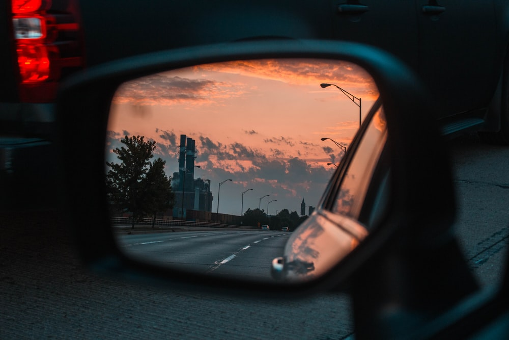 car side mirror view of road and lampposts during golden hour