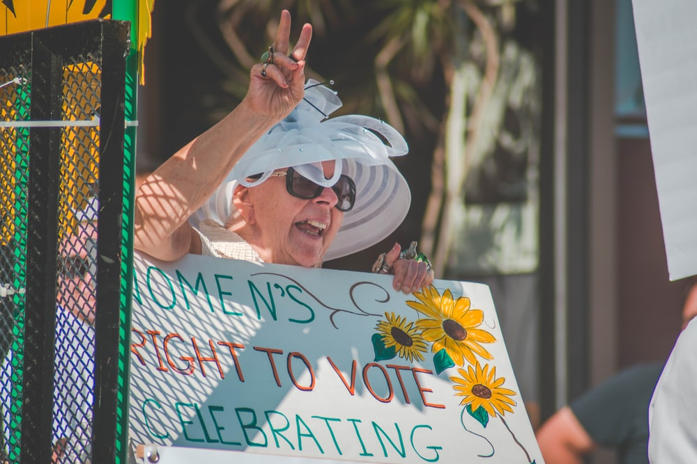 woman holding women's right to vote celebrating banner