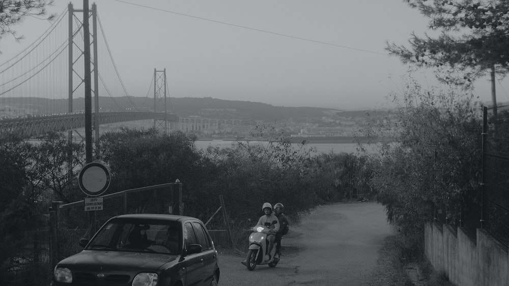 grayscale photo of men riding on motorcycle