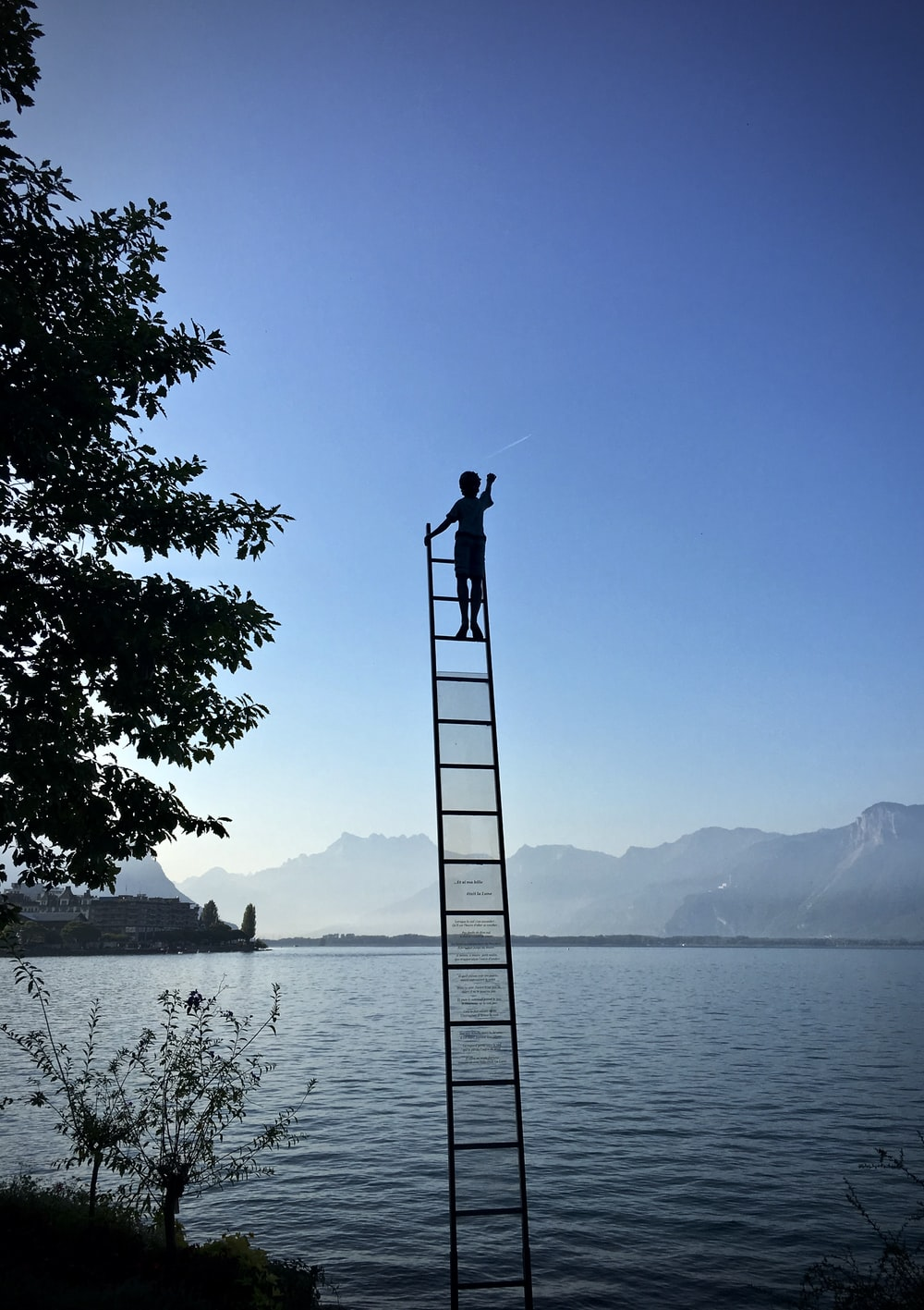 boy on ladder under blue sky