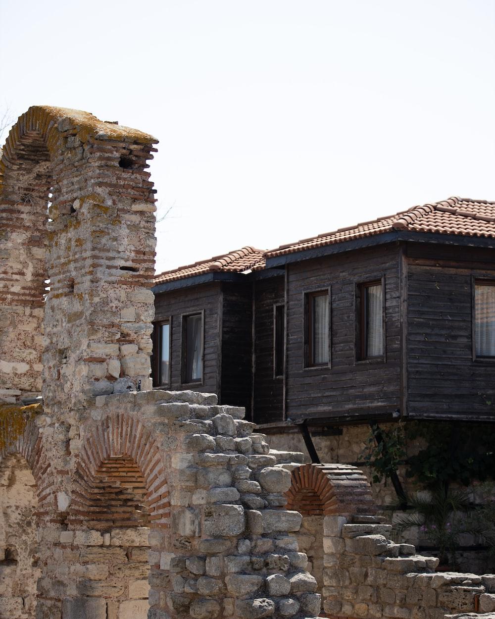 black wooden shack beside brick wall