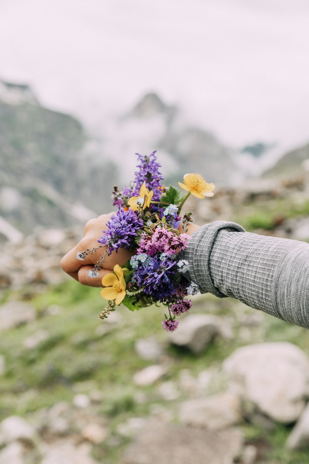 woman shows her purple and yellow flower bracelet on her wrist