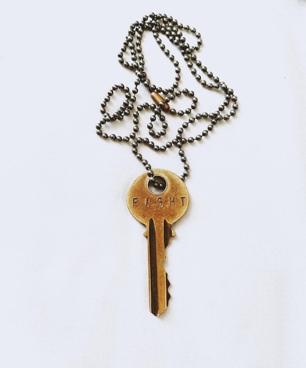 gray key fight pendant necklace on white background
