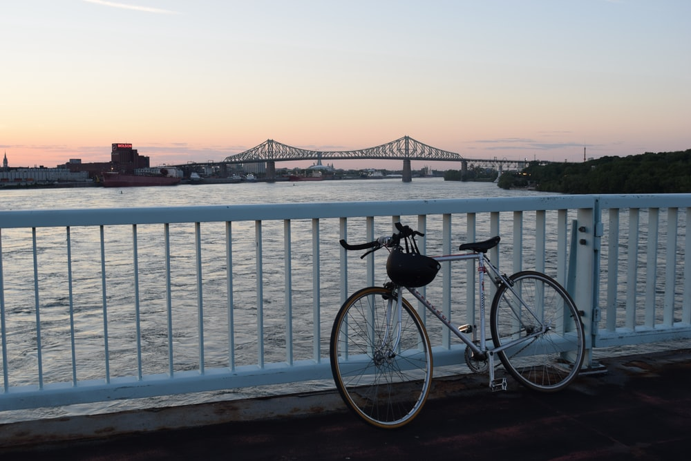 bicycle leaning on railing near water