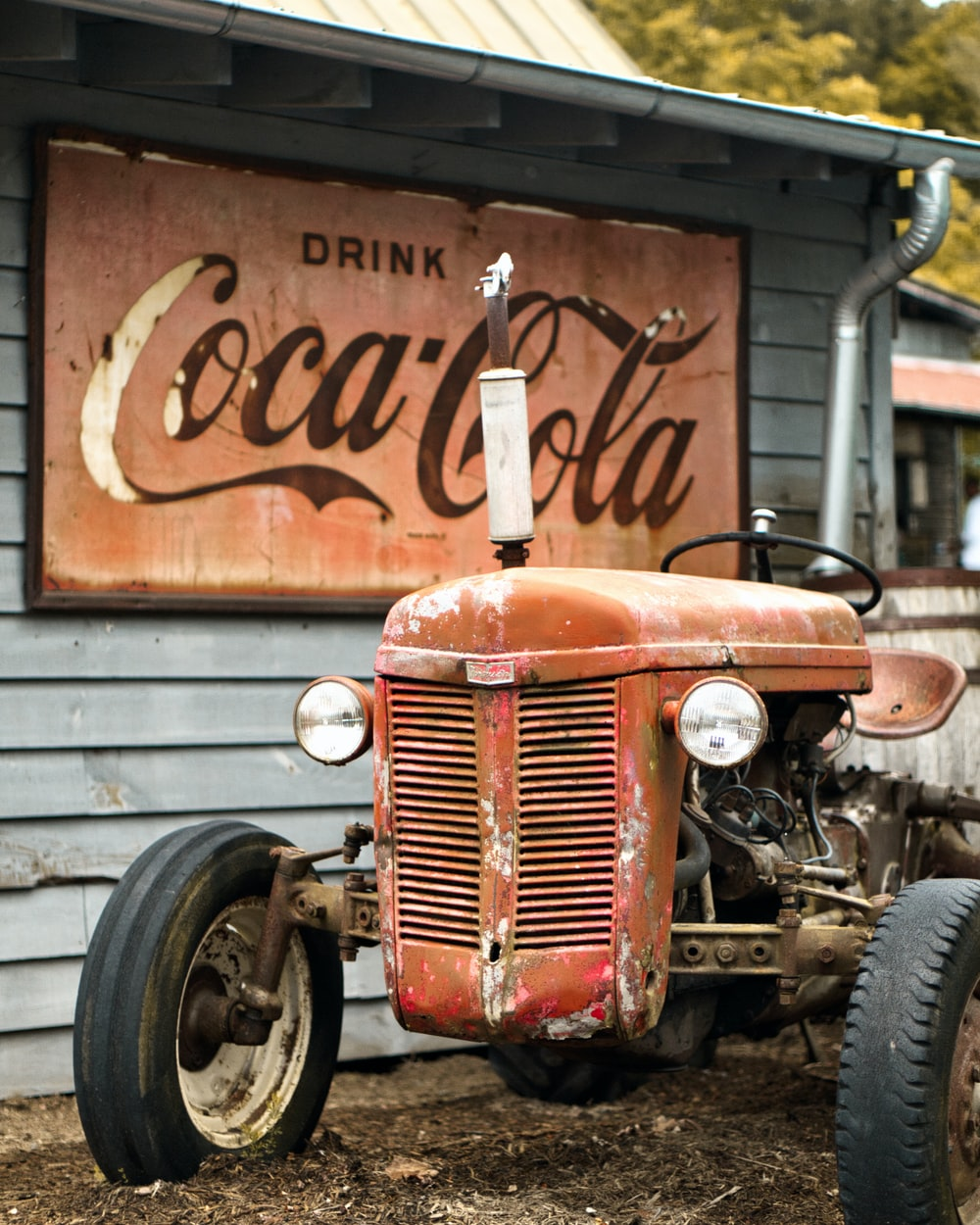 brown tractor beside Coca-Cola sign