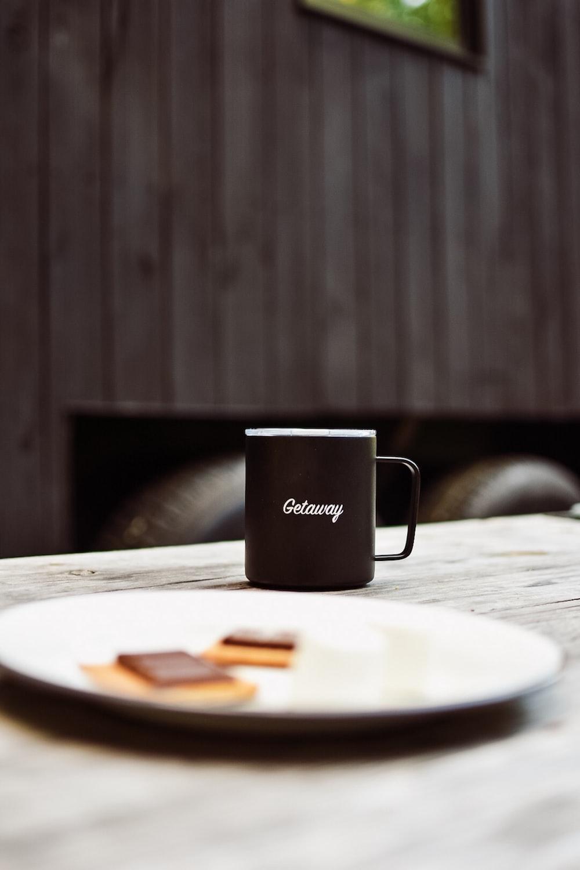 black mug beside plate