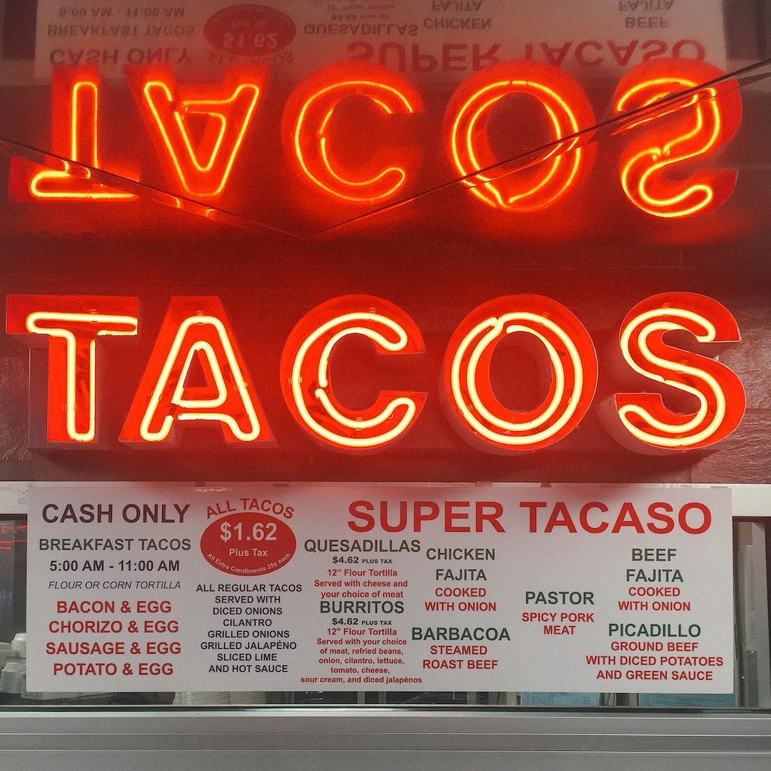 A neon taco sign above a taco menu