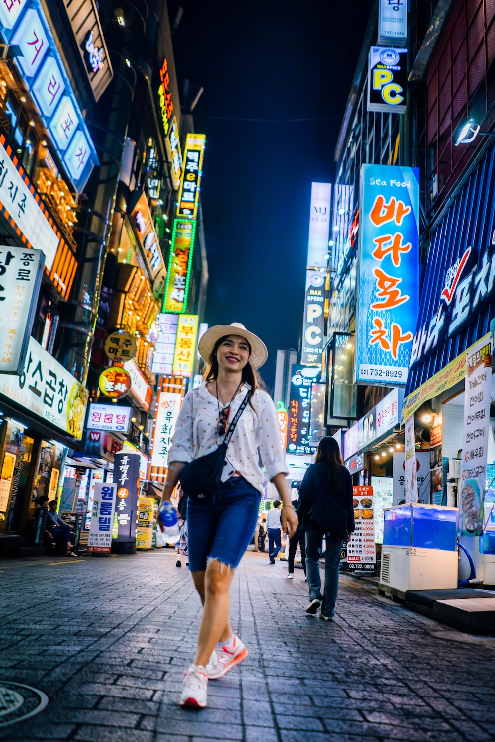 woman walking between buildings with lighted signs at night
