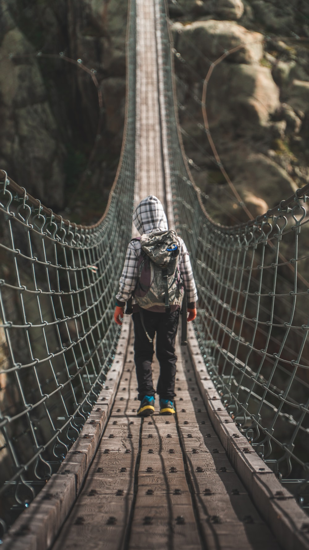 unknown person standing on gray hanging bridge