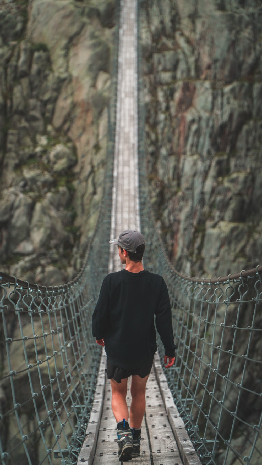 man walking on hanging bridge during daytime