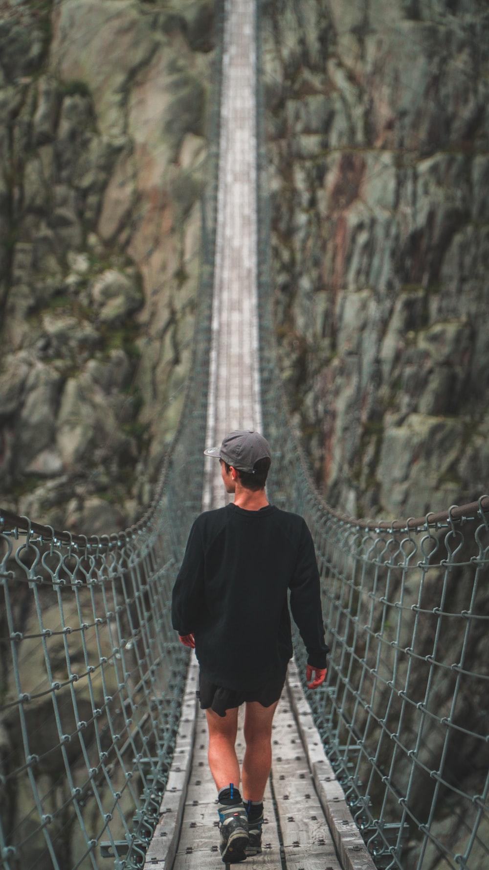 man walking on hanging bridge during daytime