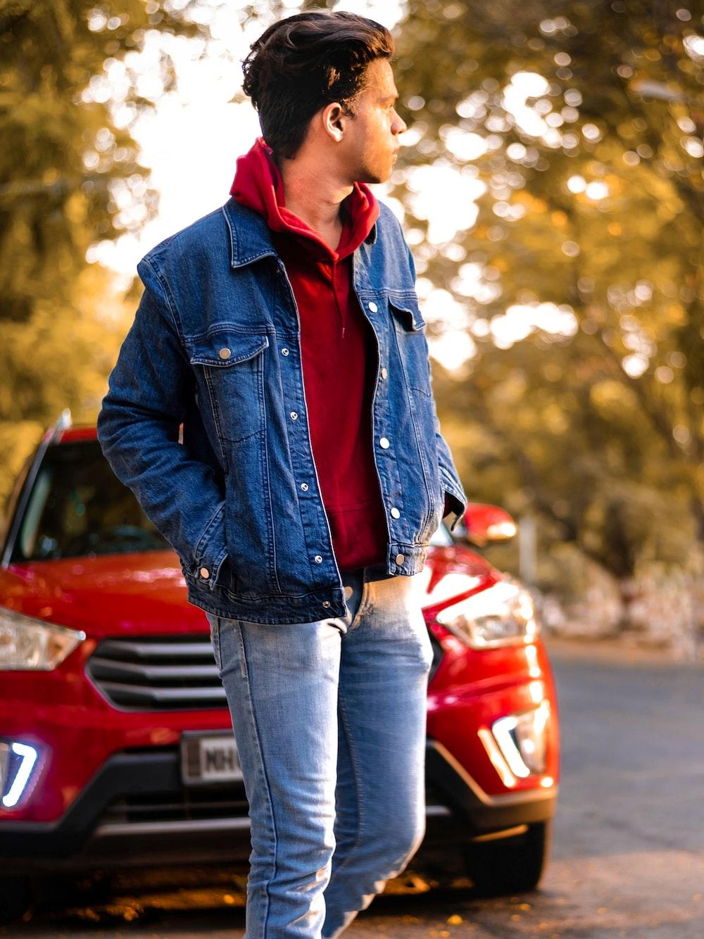 man wearing blue denim jacket standing near red vehicle beside road during daytime