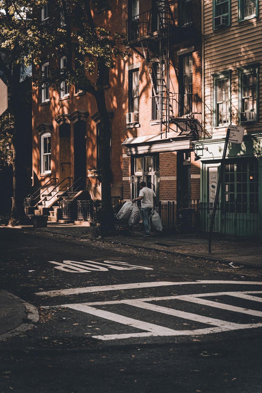 man holding white plastic bags walking near road during daytime