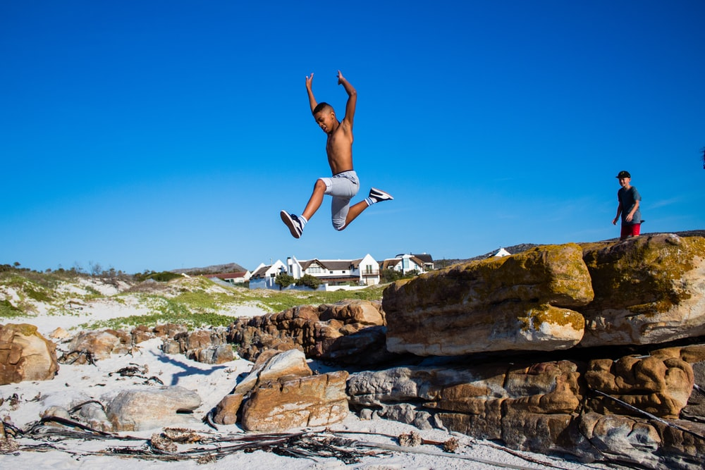 topless boy jumping from cliff under blue and white sky during daytime