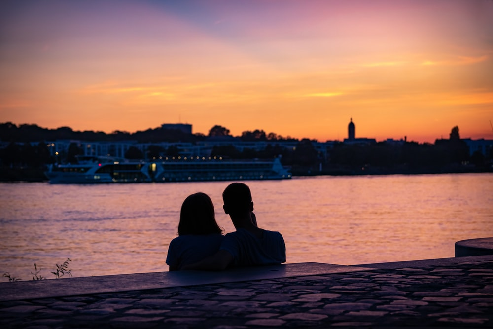 silhouette of couple sitting on shore looking at city skyline during sunset