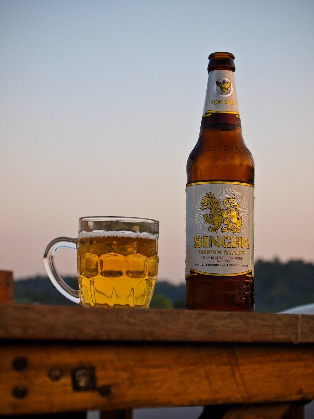 amber glass bottle beside beer mug